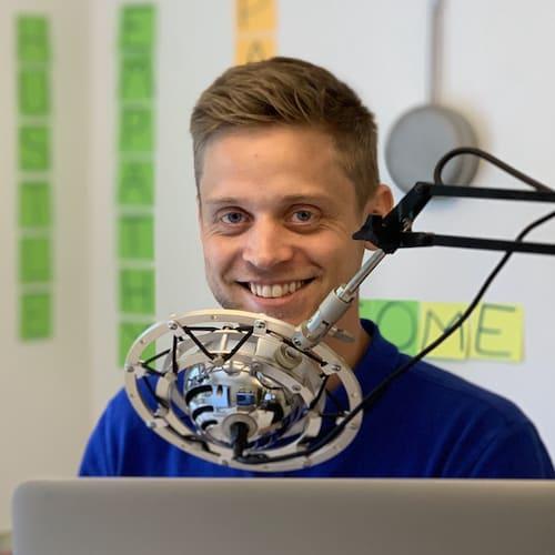 Kristian Emil Larsen smiler foran en mikrofon