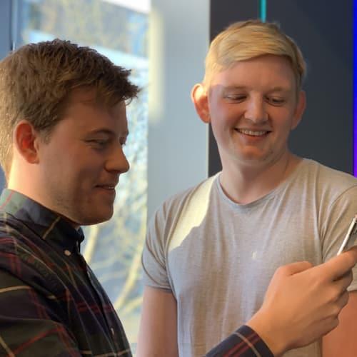 Rasmus og Alexander ser på en telefon og smiler