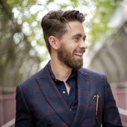 Smilende ung mand i jakkesæt
